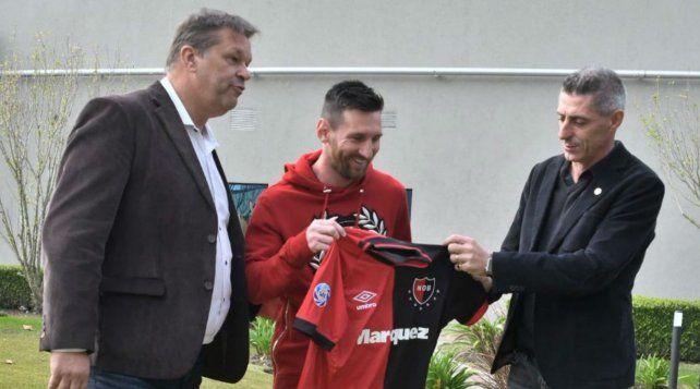 El secretario Concina y el vicepresidente DAmico le entregan a la Pulga una camiseta de Newells.