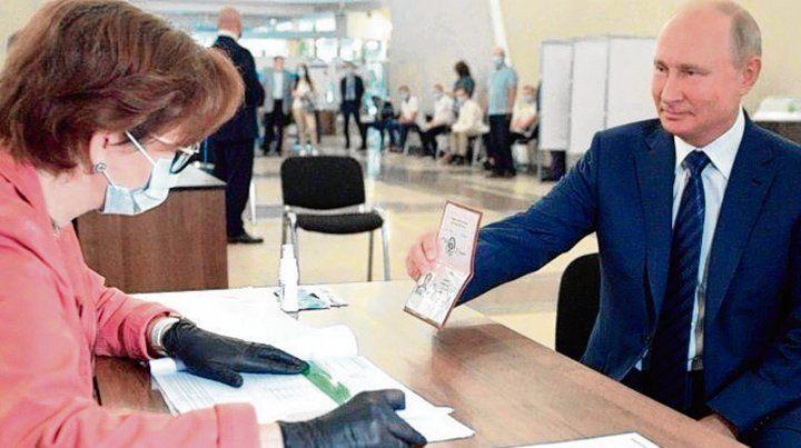 a votar. Putin muestra ayer su pasaporte a una funcionaria electoral.
