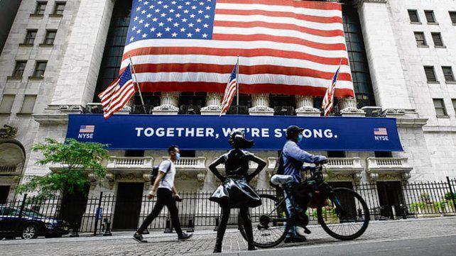 Nueva York. Peatones con barbijo pasan frente a la Bolsa neoyorkina.