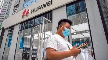Un ciudadano chino chequea su celular mientras traspone un local de Huawei en Beijing.