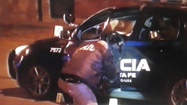 Policías peritan el móvil policial que fue atacado a balazos cuando estaba de custodia en la puerta de la casa del empresario.