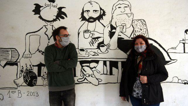 Los directivos Liliana Núñez y David Muratore junto al mural pintado por los chicos que identifica a la escuela.