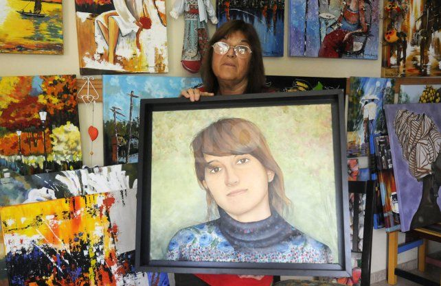 Graciela Brondino junto a la pintura de su hija Marianela.