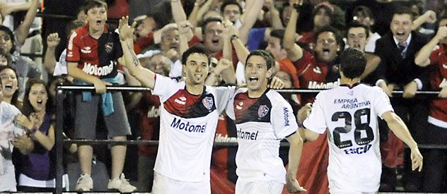 Scocco festeja el gol del triunfo con Maxi Rodríguez y Martín Tonso. (Foto: M. Sarlo)