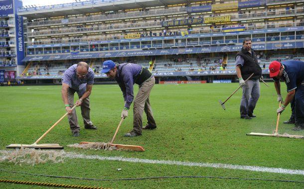 Los empleados del club xeneize sacan el agua acumulada en el campo de juego.