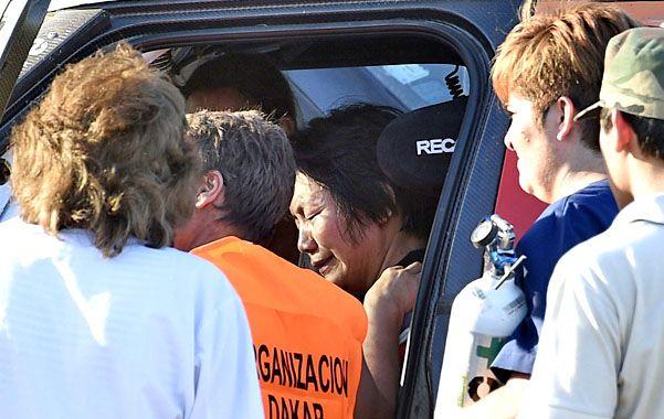 Tristeza y dolor. La piloto china apesadumbrada es asistida mientras bomberos y enfermeras retiran a los heridos.