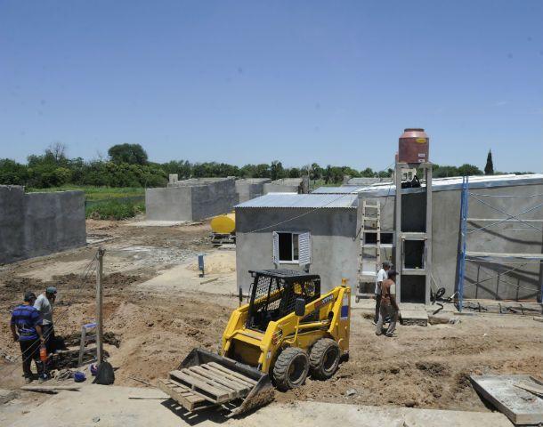 Contrastes. Operarios trabajan en la construcción de las casas donde se mudarán quienes viven a la vera de la ruta.