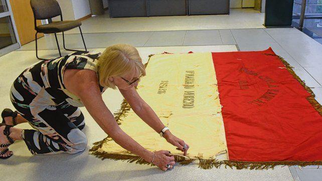 Rojo y dorado. La bandera es de seda y está bordada.