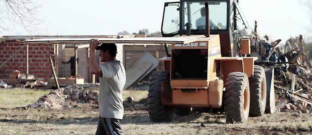 Una máquina remueve restos de viviendas
