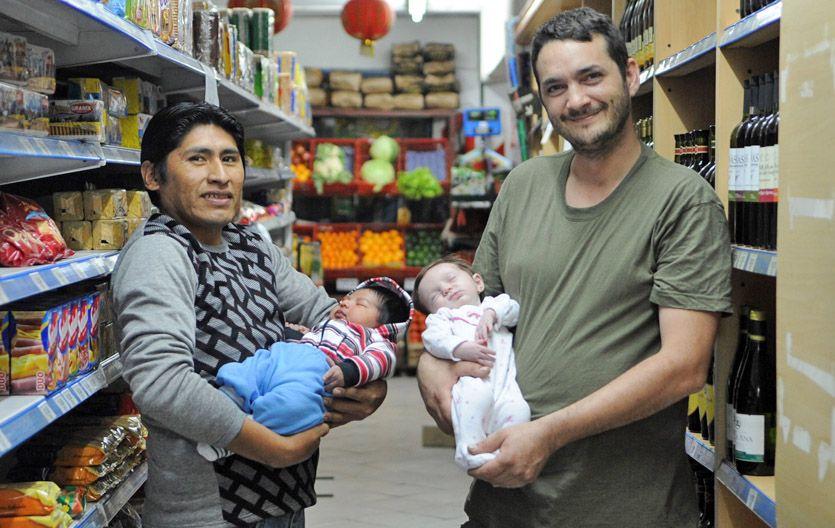 Buenos tiempos. Blas con su varón y Diego con su nena posan entre la mercadería del súper de Lagos al 8000.