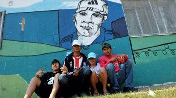 Nahuel, Javier, Seba y Chimi, en el centro de salud, junto al mural de Cachón, líder fallecido.