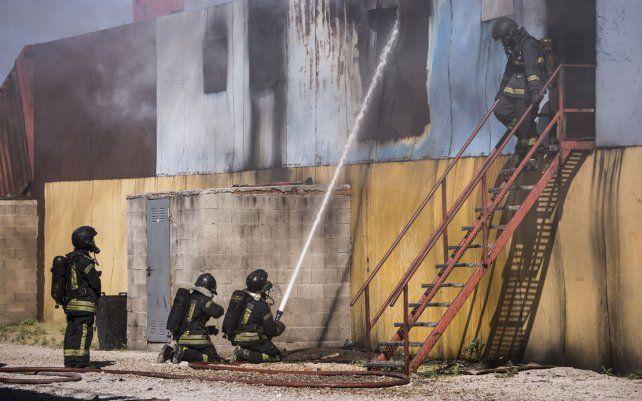 Un grupo de voluntarios trabaja en la extinción de un incendio provocado durante un simulacro como parte del nuevo curso de ingreso para 100 candidatos al Departamento de Bomberos de la Comunidad de Madrid.