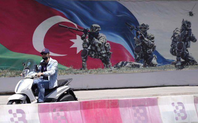 Un hombre conduce una scooter junto a un cartel antes del Gran Premio de Fórmula Uno en el circuito urbano de Fórmula Uno de Bakú en Bakú