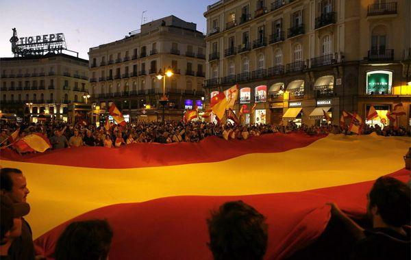 Manifestantes en la madrileña Puerta del Sol exhiben una gran bandera española.