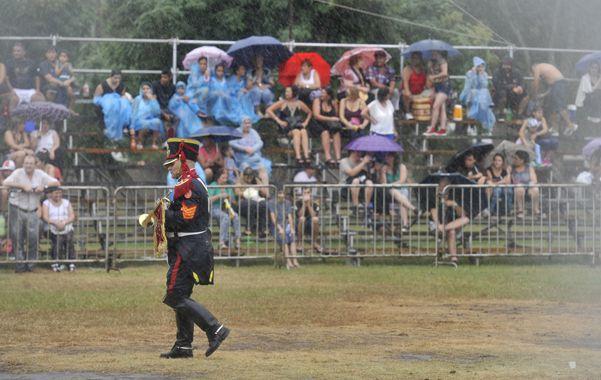 Deseos de ver el acto evocativo. Algunos asistentes se refugiaron bajo los paraguas para ver a los granaderos. (foto: Virginia Benedetto)
