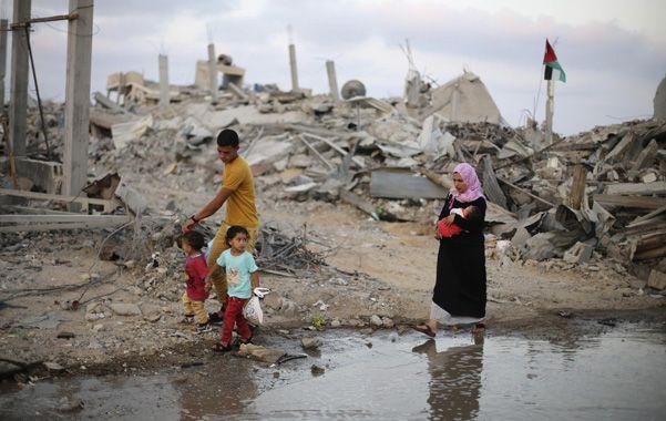 Devastación. Una familia palestina se desplaza entre las ruinas de una zona muy castigada de la Franja de Gaza.
