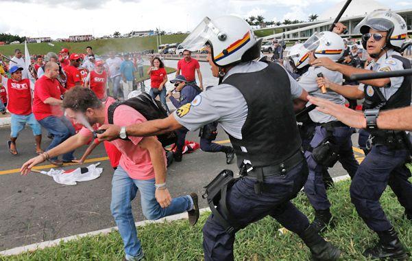 Represión. Un policía arroja gas pimienta a un manifestante frente al Parlamento en Brasilia.