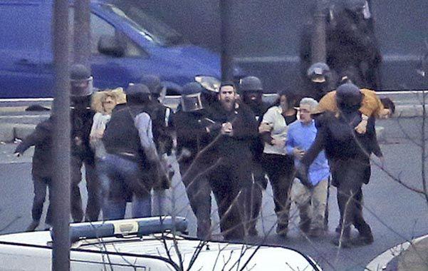 A salvo. Rehenes que pudieron ser rescatados de la tienda de comida judía son evacuados por la policía.
