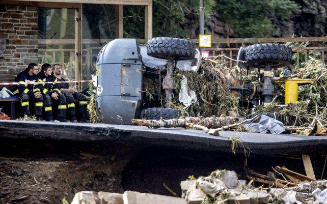 Bomberos se toman un descanso en un banco en un pueblo en el distrito de Ahrweiler mientras lidian con la devastación causada por la inundación del río Ahr en el oeste de Alemania