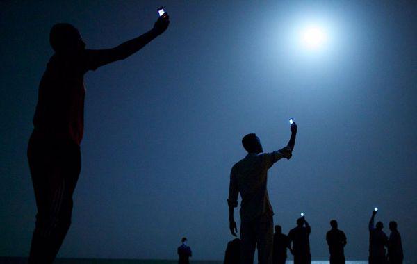 Migrantes africanos buscan señal para sus teléfonos móviles en Djibouti. Esa fotografía le valió el premio principal al estadounidense John Stanmeyer / World Press Photo