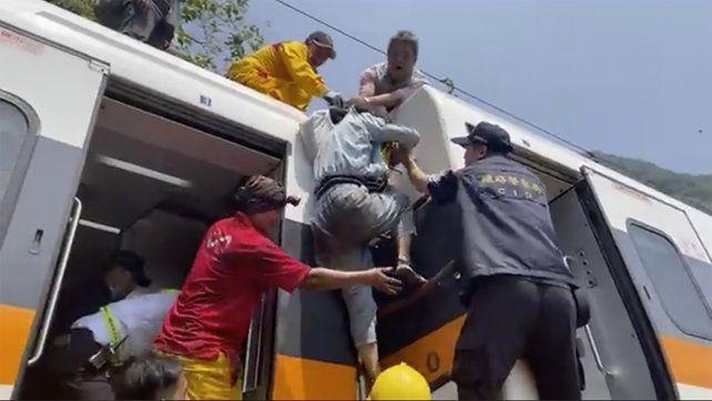 Los socorristas ayudan a una de las víctimas a salir del tres tras el violento impacto.