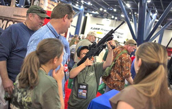 ¿Orgulloso? Un padre observa cómo su hijo apunta con un fusil de asalto (versión infantil) en una feria de armas.