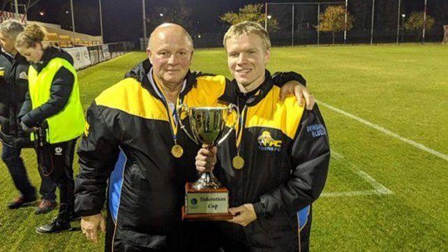 Momento feliz. Wilk luce junto a un jugador el trofeo de la FFA Cup que ganó en 2019.