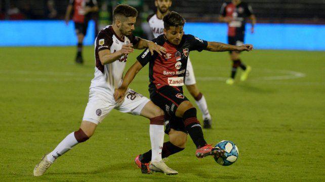 Sebastián Palacios intenta escapar a Morgantini en el triunfo 3 a 1 de Newell's a Lanús