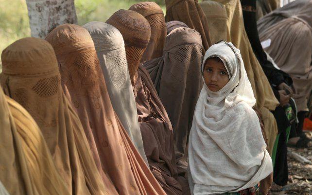 Mujeres pakistaníes esperan recibir vales en efectivo de un oficial bajo el programa de efectivo de emergencia Ehsaas del gobierno para familias necesitadas