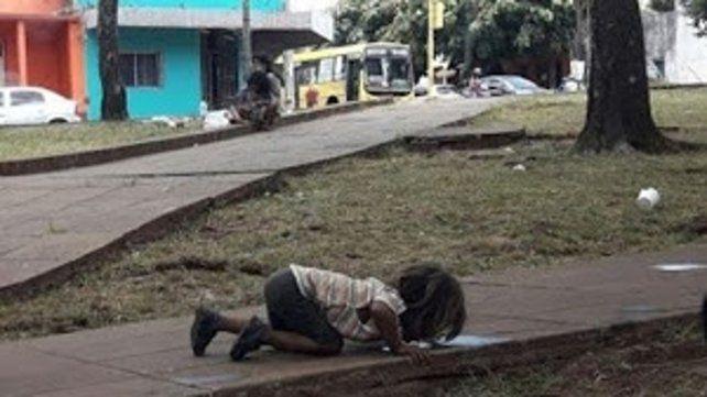 Terrible. Una niña guaraní toma agua del piso en Misiones.