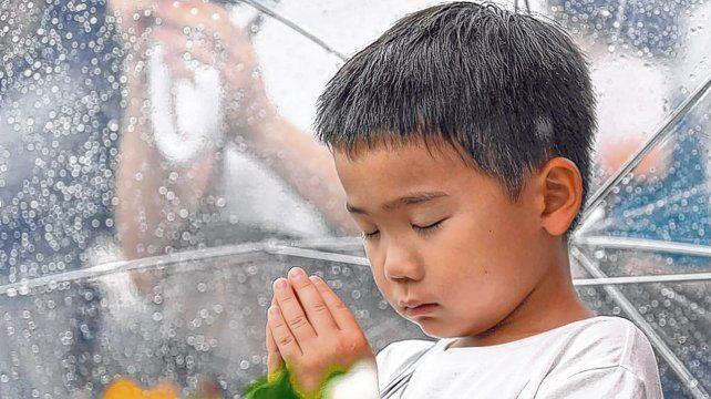 Un nene reza por las víctimas de la bomba atómica frente al cenotafio del Parque Memorial de la Paz de Hiroshima.