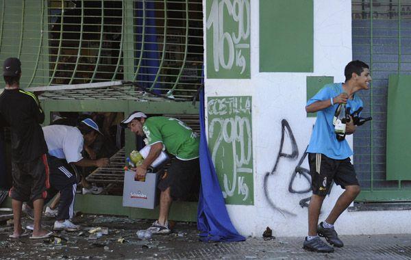 Varios jóvenes se llevan bebidas ayer en uno de los supermercados violentados. (Foto: E. Rodríguez Moreno)