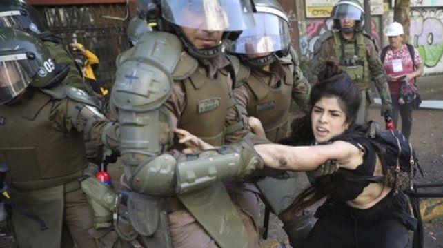 Lucha. Una manifestante es detenida ayer por la policía cerca de la Plaza Italia