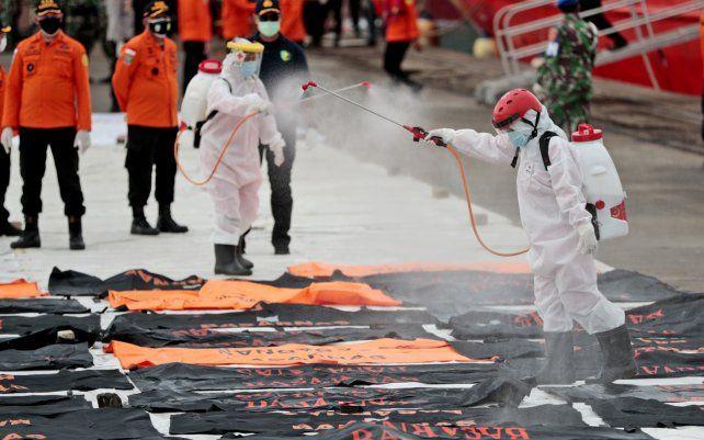 Miembros de la Cruz Roja Indonesia rocían desinfectante en bolsas para cadáveres que contienen restos humanos recuperados del mar de Java