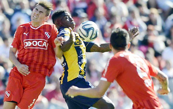 Entre dos. Valencia intenta controlar la pelota a pesar de la doble marca de Independiente.