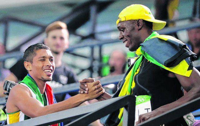 El traspaso. Bolt y van Niekerk se saludan tras ganar las medallas de oro en 100 y 400 metros el año pasado en Río.