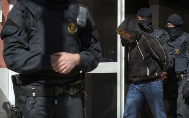 Arrestos. Uno de los terroristas es trasladado esposado en Cataluña.