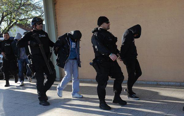 Efectivos de la Policía de Seguridad Aeroportuaria trasladan a los detenidos en el aeropuerto Islas Malvinas.