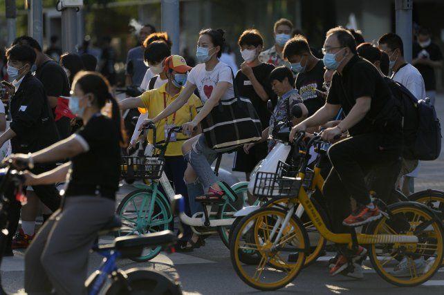 Ciclistas con barbijos este lunes en una calle de Beijing. Esta ciudad y otras 20 están bajo régimen de confinamiento.