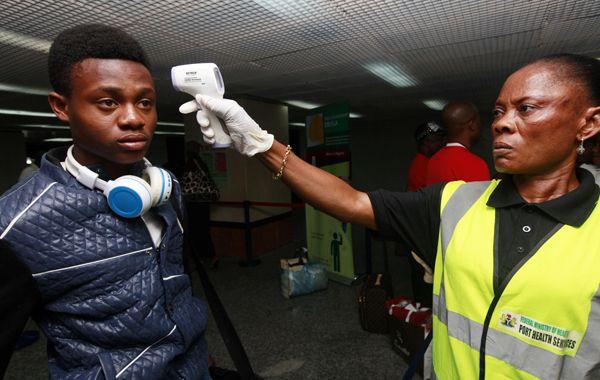 Una agente de salud controla la temperatura de un pasajero en el aeropuerto de Lagos.