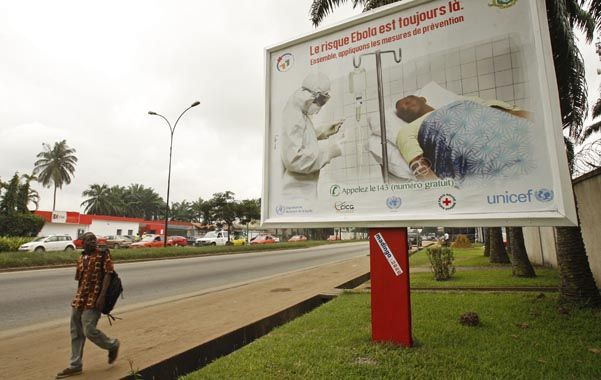 Prevención. Un habitante camina delante de un cartel de la campaña contra el ébola