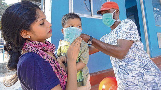 llegó la enfermedad. Un asistente le coloca el barbijo a un bebé en Kerala
