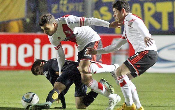 Fricción. Bertolo disputa la pelota con Cervi. Mora sigue la jugada de cerca.
