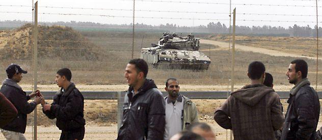 Fuerzas de Hamas vigilan el cerco fronterizo. Un tanque israelí toma posición defensiva.