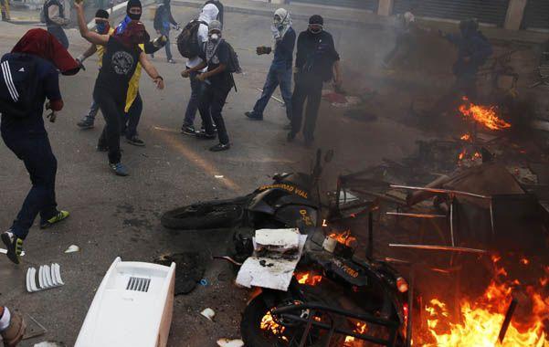 Irracional. Opositores al gobierno queman una moto de la Guardia Nacional.