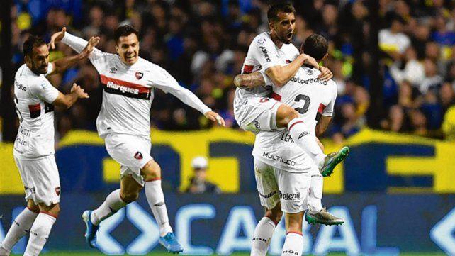 Subido al festejo. Villarruel trepa sobre la humanidad de Lema en el gol leproso.