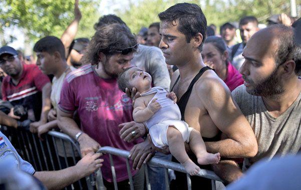 Un hombre sostiene a su pequeño en brazos mientras implora a un guardia fronterizo croata que lo deje cruzar.