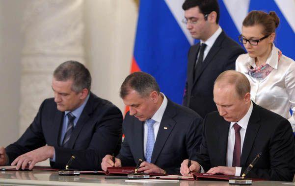 Otra vez rusa. Putin (der.) suscribe el tratado junto a los líderes de Crimea y de la ciudad portuaria de Sebastopol.