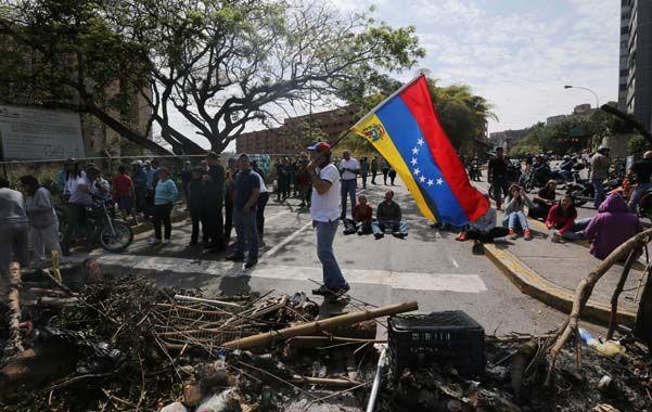 Resistencia callejera. Opositores ante los restos de una barricada nocturna en una avenida de Caracas.