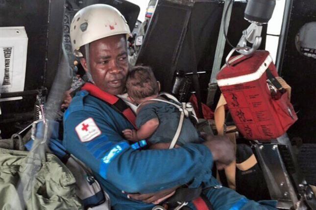 Salvador. Acisclo Rentería sostiene en brazos a Yudier en el helicóptero que los trasladó a un hospital.